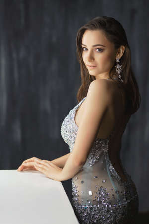 Beautiful young woman posing in a studio near the table dressed in a blue silver dress with stones