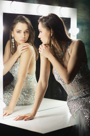 Alluring young brunette posing in a studio sitting on a table looking into mirrors dressed in an elegant blue silver dress with stones.