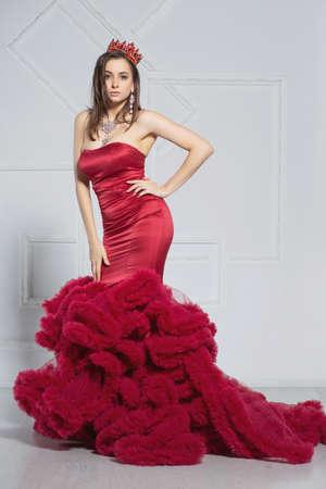 Schöne junge Dame posiert in einem Studio in einem eleganten roten Kleid und einer Krone