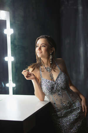 Attractive young woman posing in a studio near the table dressed in a blue silver dress with stones Stock Photo