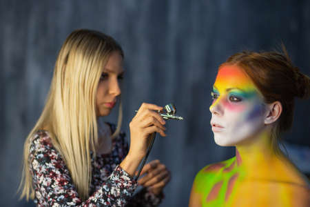 The artist puts a face painting on a nice young model in the studio, against a gray wall