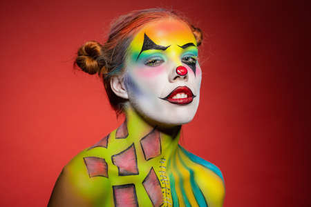 Pensive young lady with a face painting clown posing in the studio on a red background
