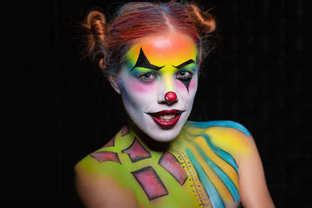 Cute woman with a body art clown posing in the studio on a black background
