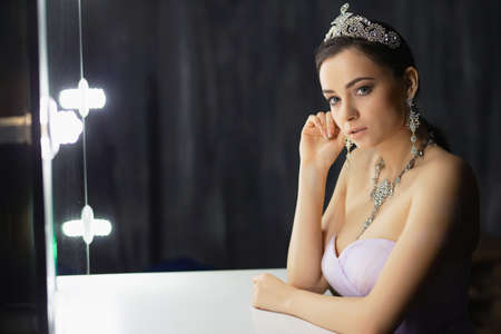 Beautiful lady posing in a studio near the table wearing a dress and a crown