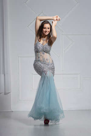 Adorable young woman poses in a studio dressed in an elegant blue silver dress with stones Stock Photo