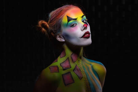 Beautiful young woman with a face painting clown posing in the studio on a black background