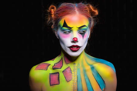 Beautiful lady with a face painting clown posing in the studio on a black background Stock Photo - 128743302