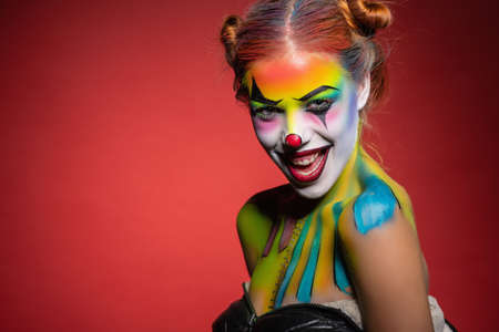 Beautiful young lady with a face painting clown posing in the studio on a red background
