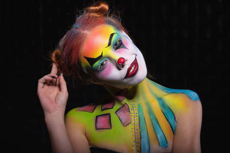 Cute lady with a face painting clown posing in the studio on a black background Stock Photo - 128752522