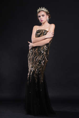 Young adorable woman posing in studio dressed in an evening black dress with a gold pattern and a crown
