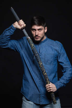Handsome young man posing in studio holding a katana in his hands, dressed in a jeans shirt