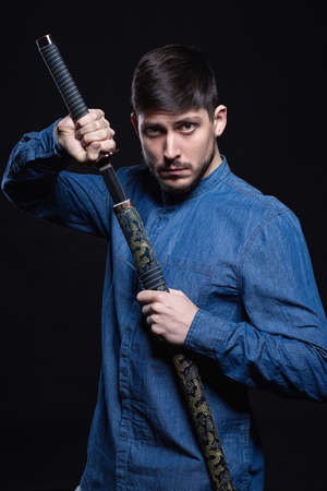 Attractive young man posing in studio holding a katana in his hands, dressed in a jeans shirt