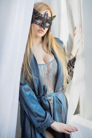 Young lovely lady in a mask posing near the window, dressed in a bodysuit and bathrobe
