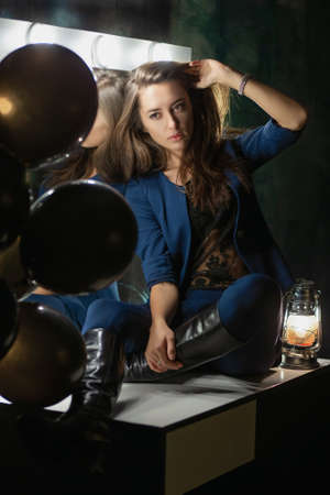 Pretty young lady posing while sitting on a table near a mirror and balloons dressed in a blue suit