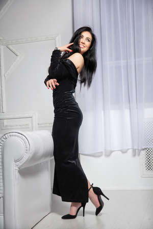 Sexy woman posing in studio standing near the sofa dressed in a black evening dress