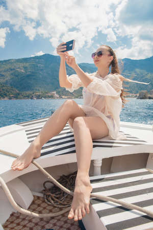Young attractive brunette takes a selfie on a yacht on a background of mountains and the sea, dressed in a swimsuit and tunic
