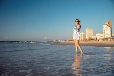 Beautiful woman posing on the beach standing in the water, wearing a tunic and glasses