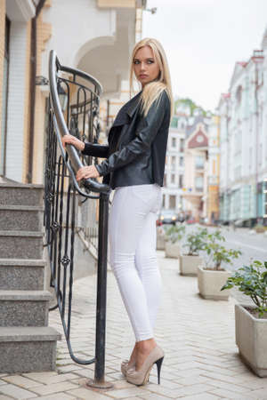 Cute blonde posing near the stairs on the background of buildings, dressed in a jacket, pants and corset Фото со стока