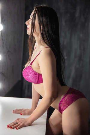 Portrait of a lovely brunette dressed in lingerie posing at the table