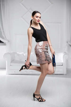 Adorable lady dressed in a shirt and skirt with sequins posing in the studio