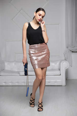 Cute lady dressed in a shirt and skirt with sequins posing in the studio