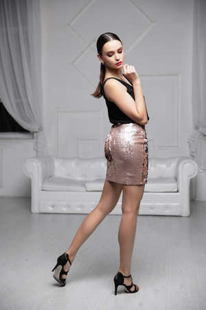 Charming lady dressed in a shirt and skirt with sequins posing in the studio