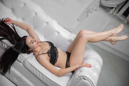 Beautiful brunette dressed in black underwear posing on a sofa Stock Photo
