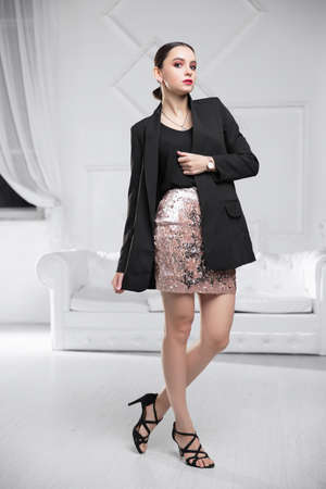Nice woman wearing a jacket, shirt and skirt posing in a studio
