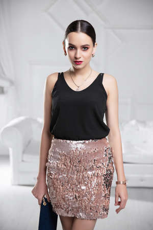 Portrait of a beautiful lady dressed in a shirt and skirt with sequins posing in the studio Stock Photo