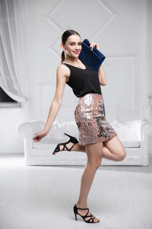 Attractive lady dressed in a shirt and skirt with sequins posing in the studio
