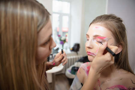 The artist applies makeup to a beautiful young model in the studio