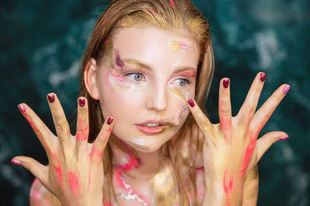 Portrait of a pretty young woman with creative make up on her face