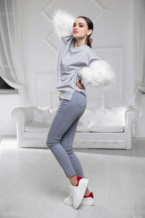 Lovely woman wearing a sweater with fur and jeans posing in studio