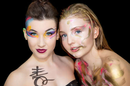 Two pretty young women with creative make-up on the face posing in the studio.