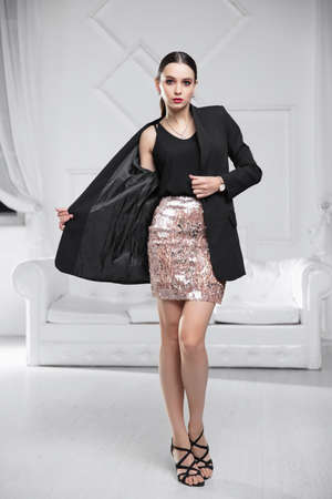 woman wearing a jacket, shirt and skirt posing in a studio