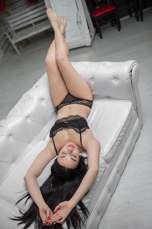 Lovely brunette dressed in black underwear posing on a sofa