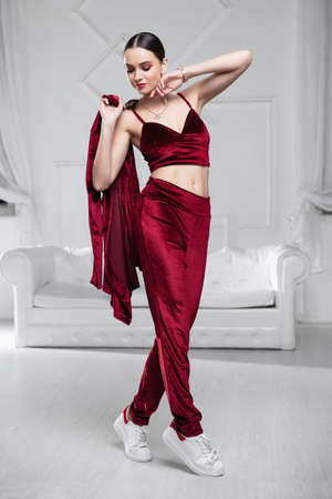 woman dressed in a burgundy velvet suit posing in the studio Stock Photo