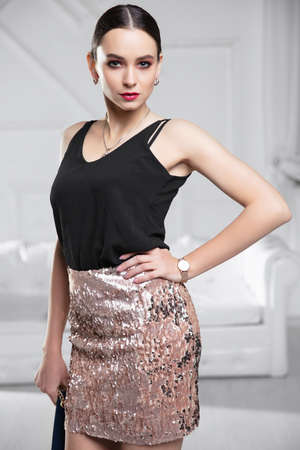Portrait of a cute lady dressed in a shirt and skirt with sequins posing in the studio