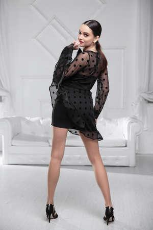 Charming woman wearing? black dress posing in the studio