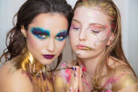 Two nice young women with creative make-up on the face posing in the studio. Stock Photo