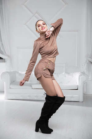 Adorable lady dressed in a blouse and shorts posing in the studio Stock Photo
