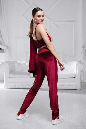 Alluring woman dressed in a burgundy velvet suit posing in the studio