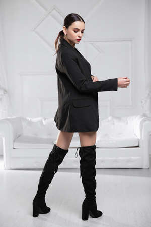 Young attractive woman wearing a jacket, shirt and skirt posing in a studio Stock Photo