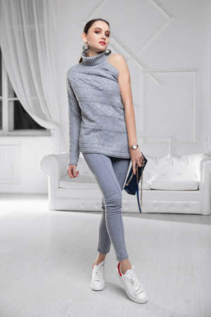 Cute lady dressed in a sweater and jeans with a blue clutch in her hands