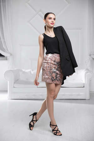 Cute woman wearing a jacket, shirt and skirt posing in a studio