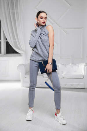 lady dressed in a sweater and jeans with a blue clutch in her hands
