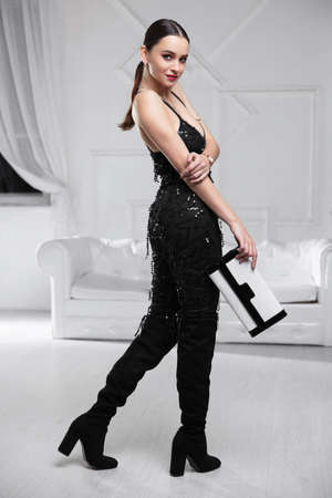 Cute young woman dressed in black overalls with clutch posing in studio