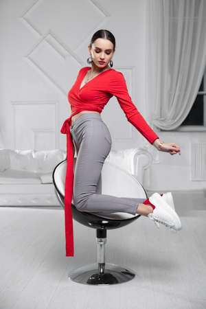 Alluring lady wearing aa red blouse and jeans posing in the studio