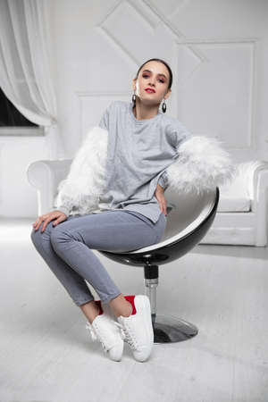 Adorable brunette wearing a sweater with fur and jeans sitting on an armchair