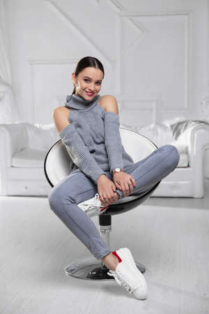 Pretty brunette wearing a gray sweater and jeans posing in studio Stock Photo